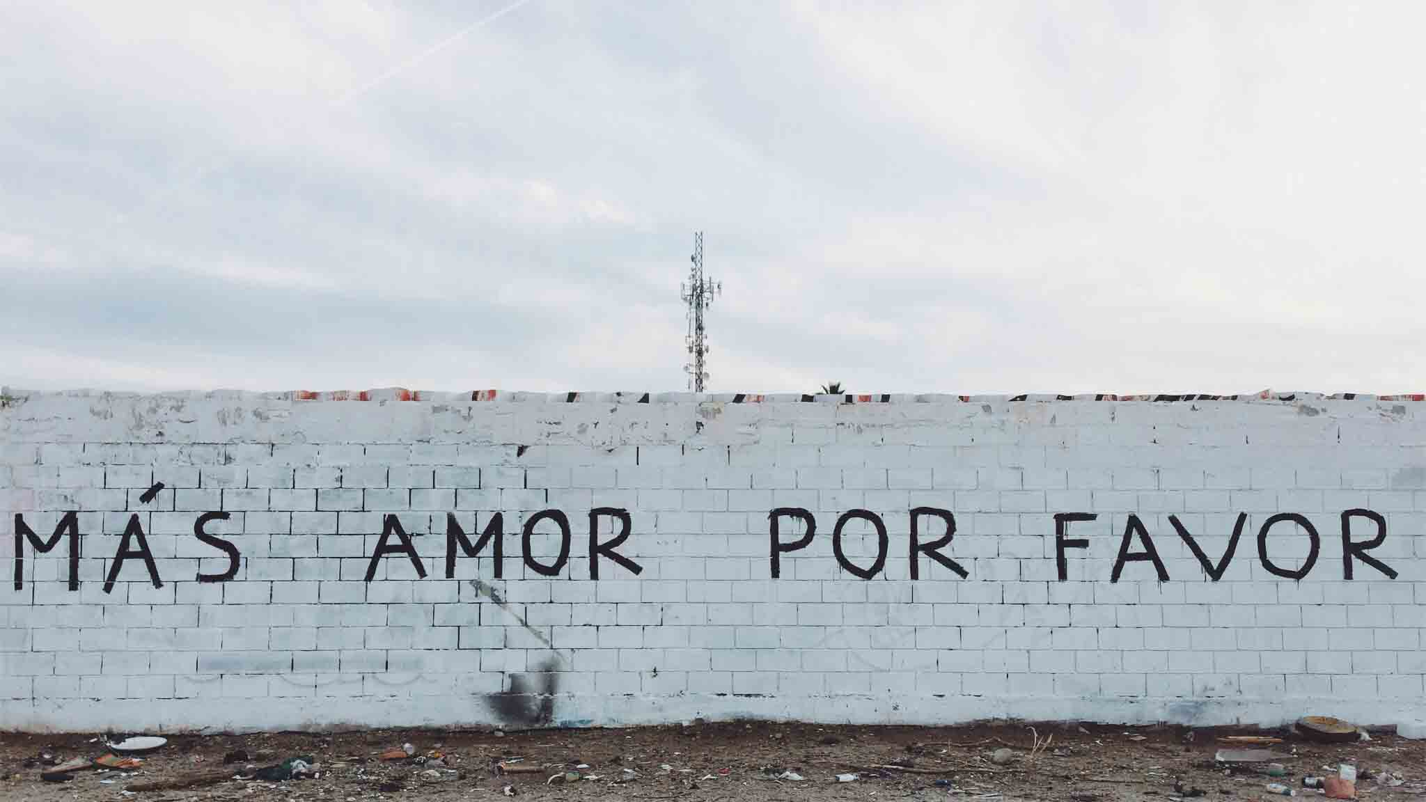 Wall with Spanish words 'Mas amor por favour'.